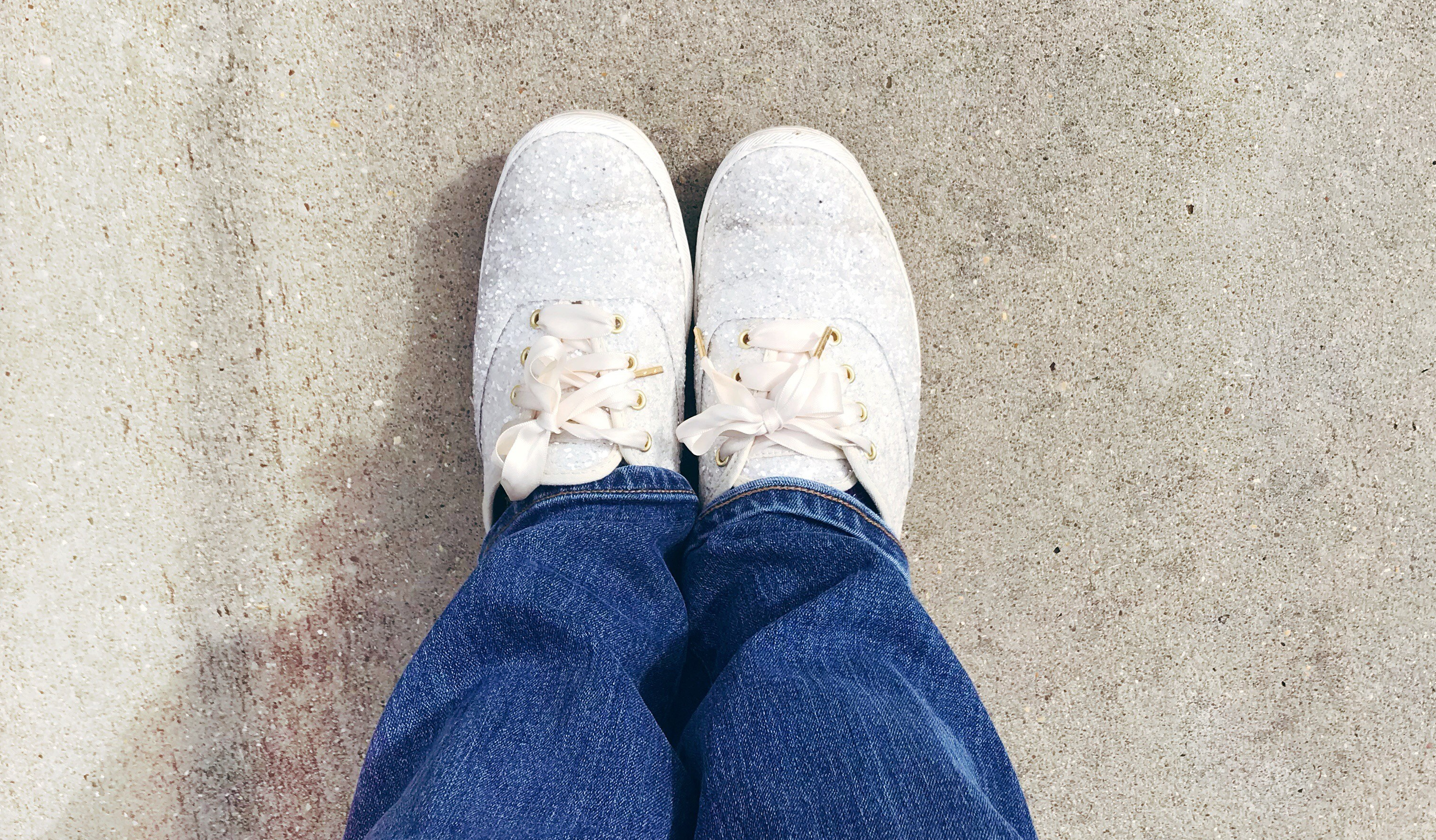 white glitter shoes on concrete